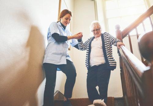 Nurse helping senior on the stairs