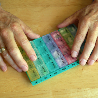 A rainbow coloured plastic weekly medication organizer.
