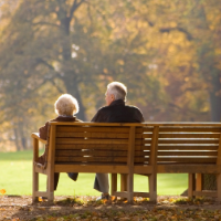Two seniors sitting on a bench in a park.