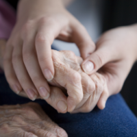 An elderly person's hand held by younger looking hands.