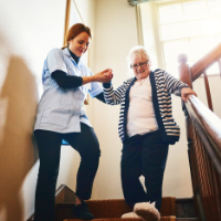 Nurse helping senior woman down the stairs.